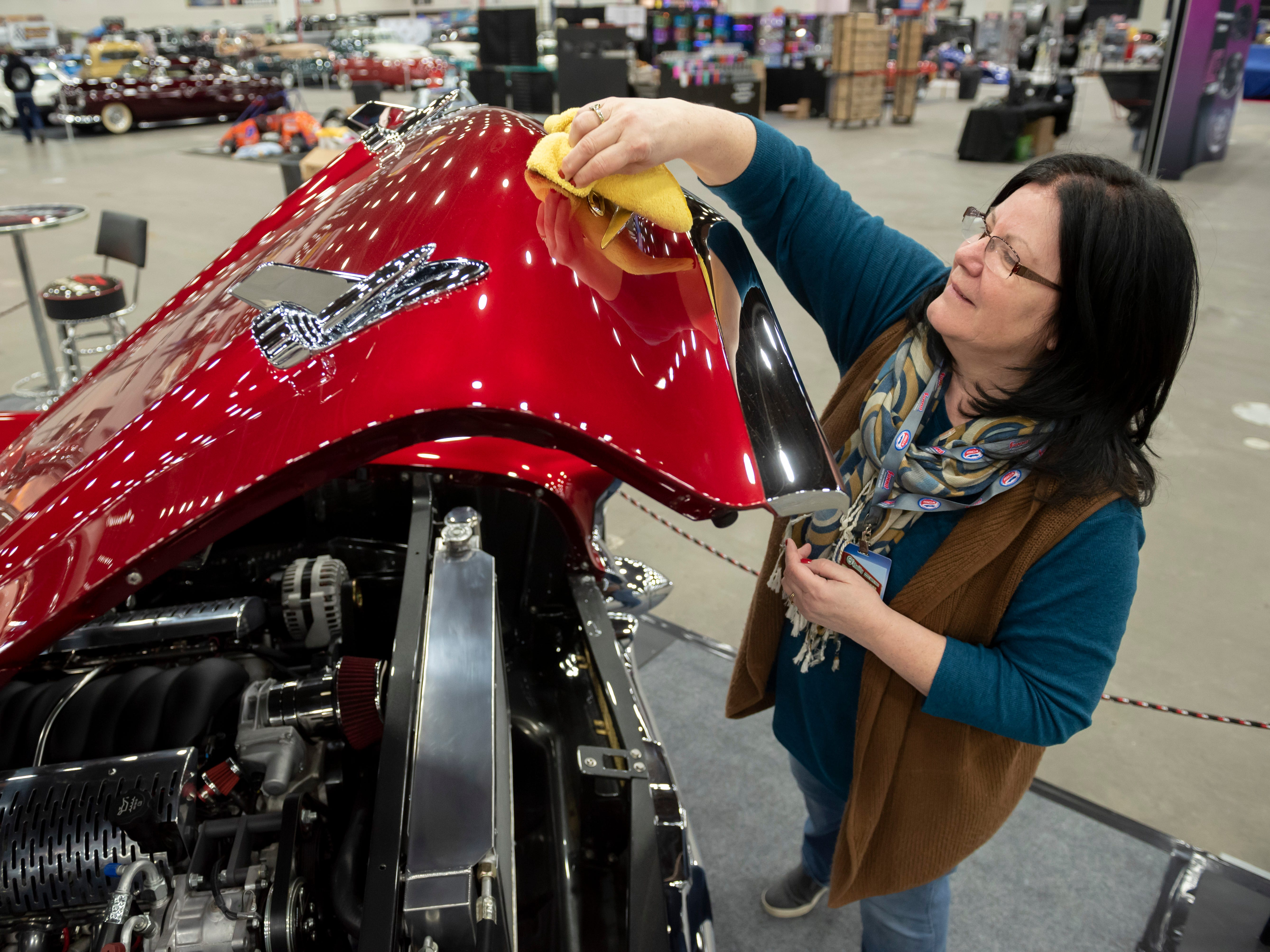 Patty Wiegand, of Richmond, polishes the hood of her 1957 Chevy Bel Air convertible.
