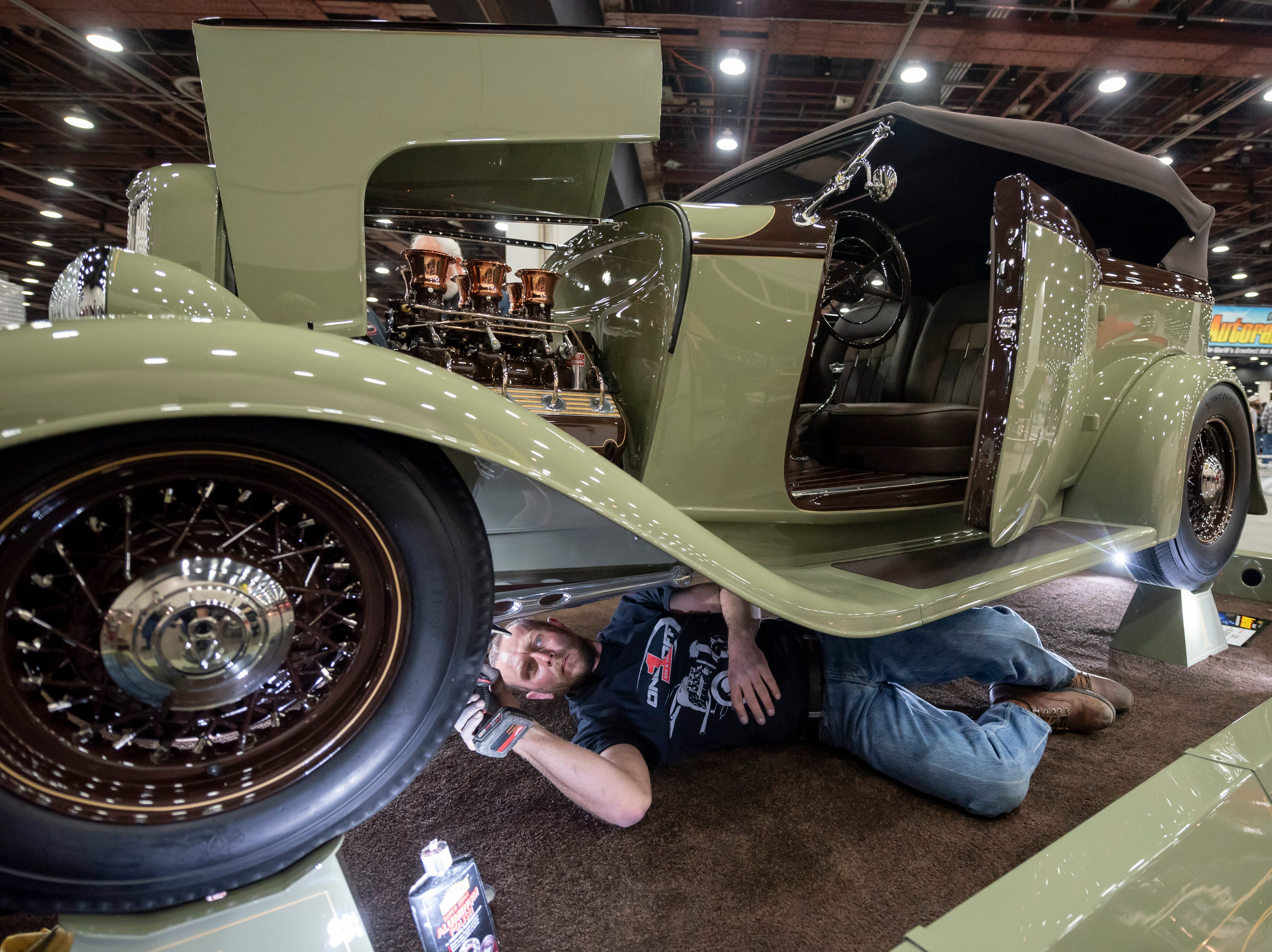 Mechanic Donnie Reeder polishes the undercarriage of a 1932 Rolls-Royce Phantom III, owned by One Off Rod & Custom, of Middletown, Delaware, during a set-up day at Detroit Autorama.