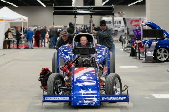 Summit Racing Equipment employees John Harms, left, and Jim Greenleaf push a nitro-fuel altered drag car being steered by Tommy Dupree towards their stand during a set up day for Autorama at Cobo Center, in Detroit, February 28, 2019.