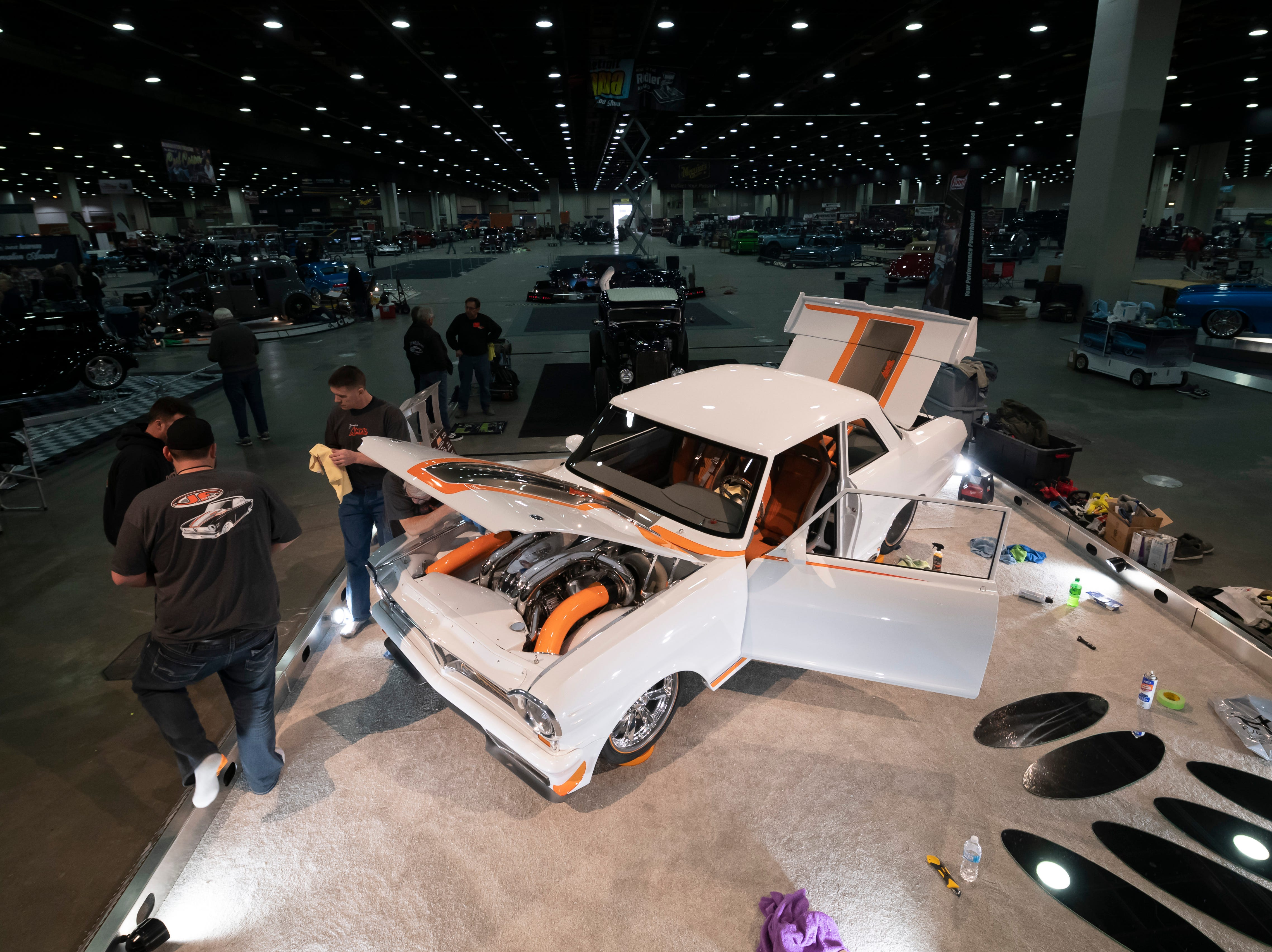 A 1964 Pontiac Acadian, owned by Danny, Sandy, and Cody Jadresko, is prepared for display during set-up day at Detroit Autorama auto show at Cobo Center.
