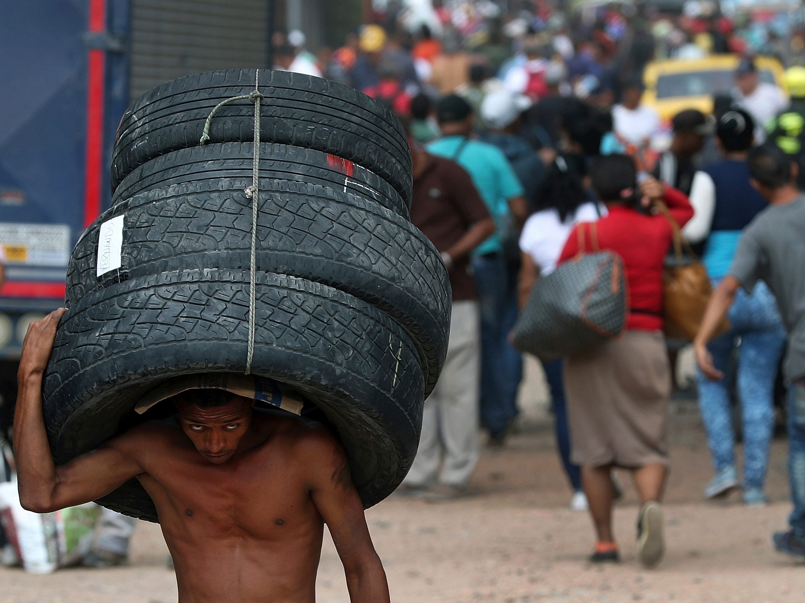 A man carries a set of used tires into Venezuela from Colombia through a blind spot on the border near the Simon Bolivar International Bridge in La Parada, Colombia, Thursday, Feb. 28, 2019.