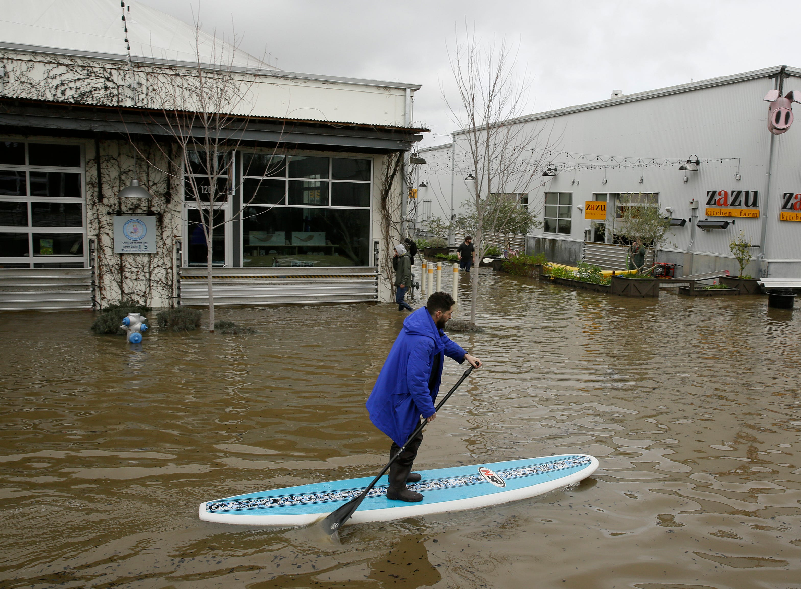 A man uses a paddle board to make his way through the flooded Barlow Market District Wednesday, Feb. 27, 2019, in Sebastopol, Calif.