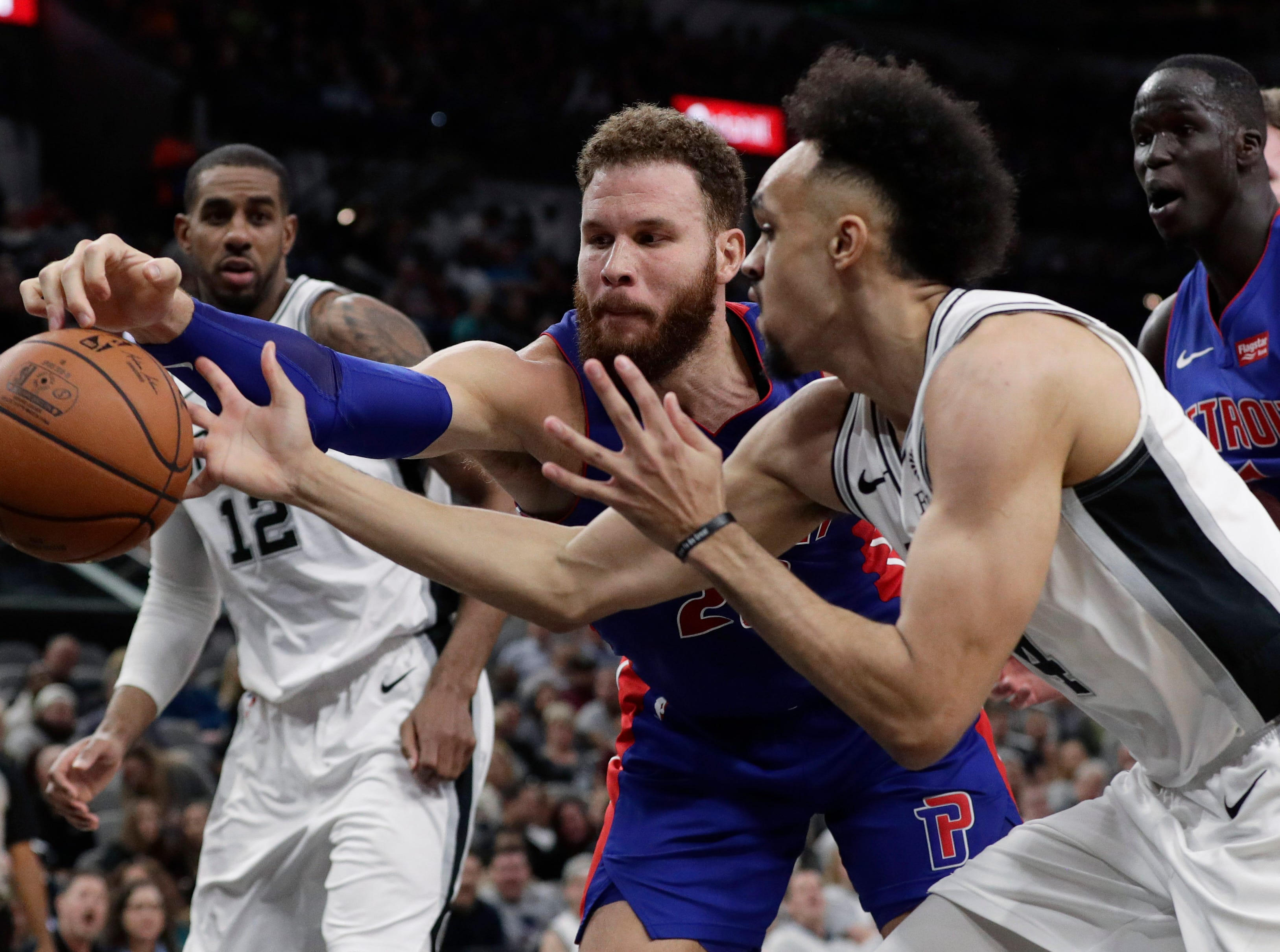 Detroit Pistons forward Blake Griffin, center, and San Antonio Spurs guard Derrick White, right, reach for the ball during the first half.