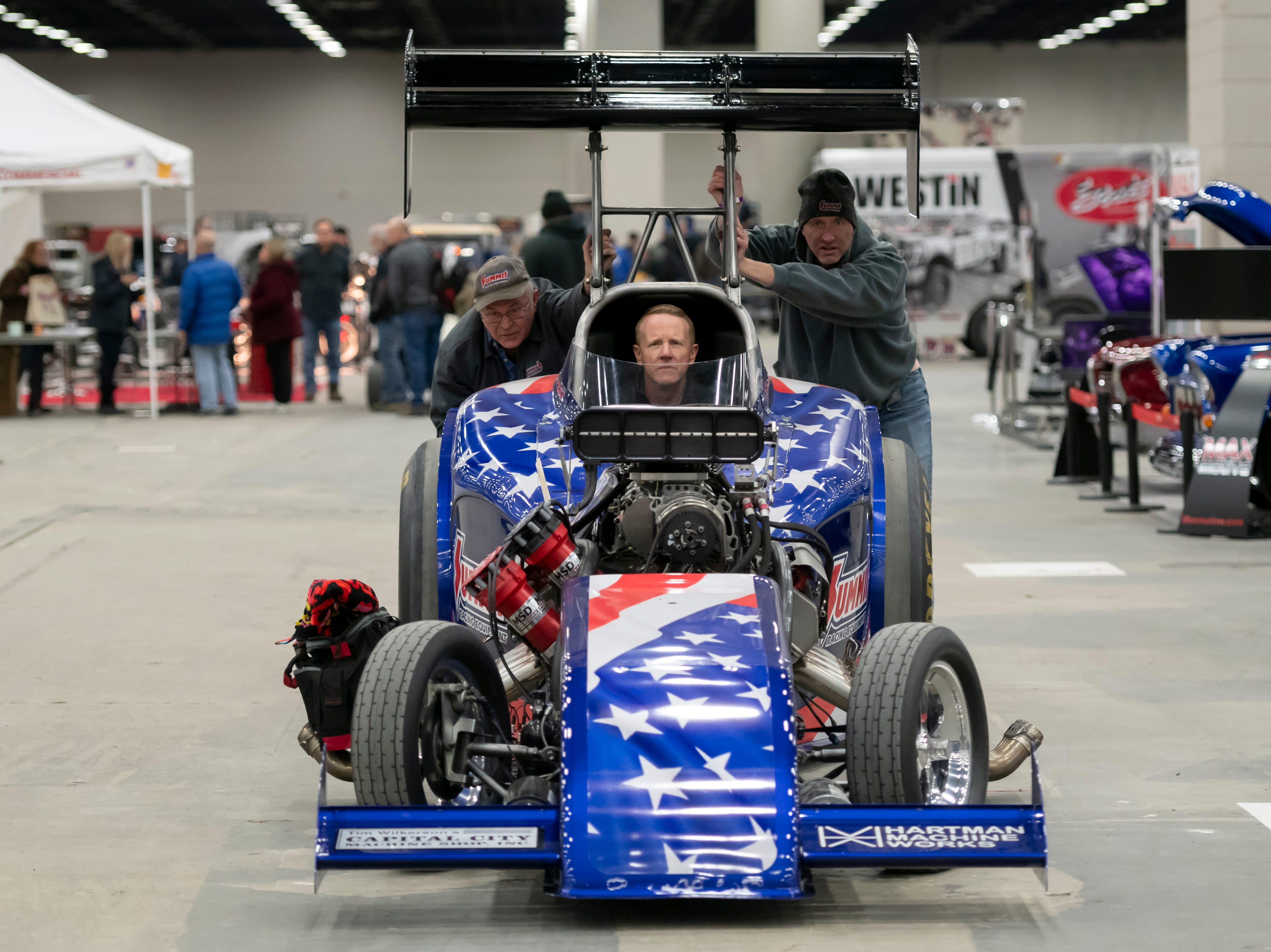 Summit Racing Equipment employees John Harms, left, and Jim Greenleaf push a nitro-fuel altered drag car being steered by Tommy Dupree towards their stand during a set up day for Detroit Autorama.