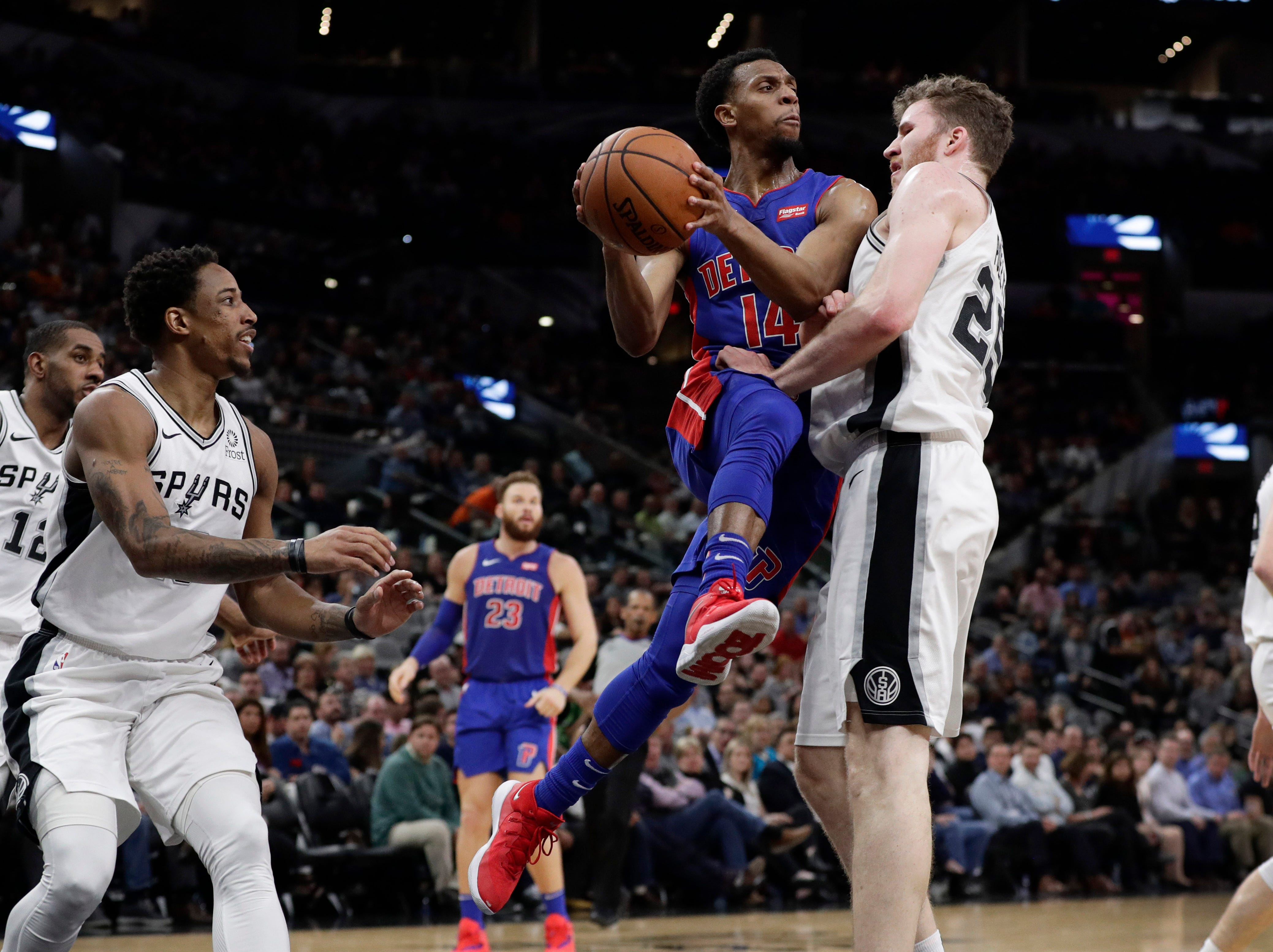 Detroit Pistons guard Ish Smith (14) crashes into San Antonio Spurs center Jakob Poeltl (25) as he drives with ball during the first half.