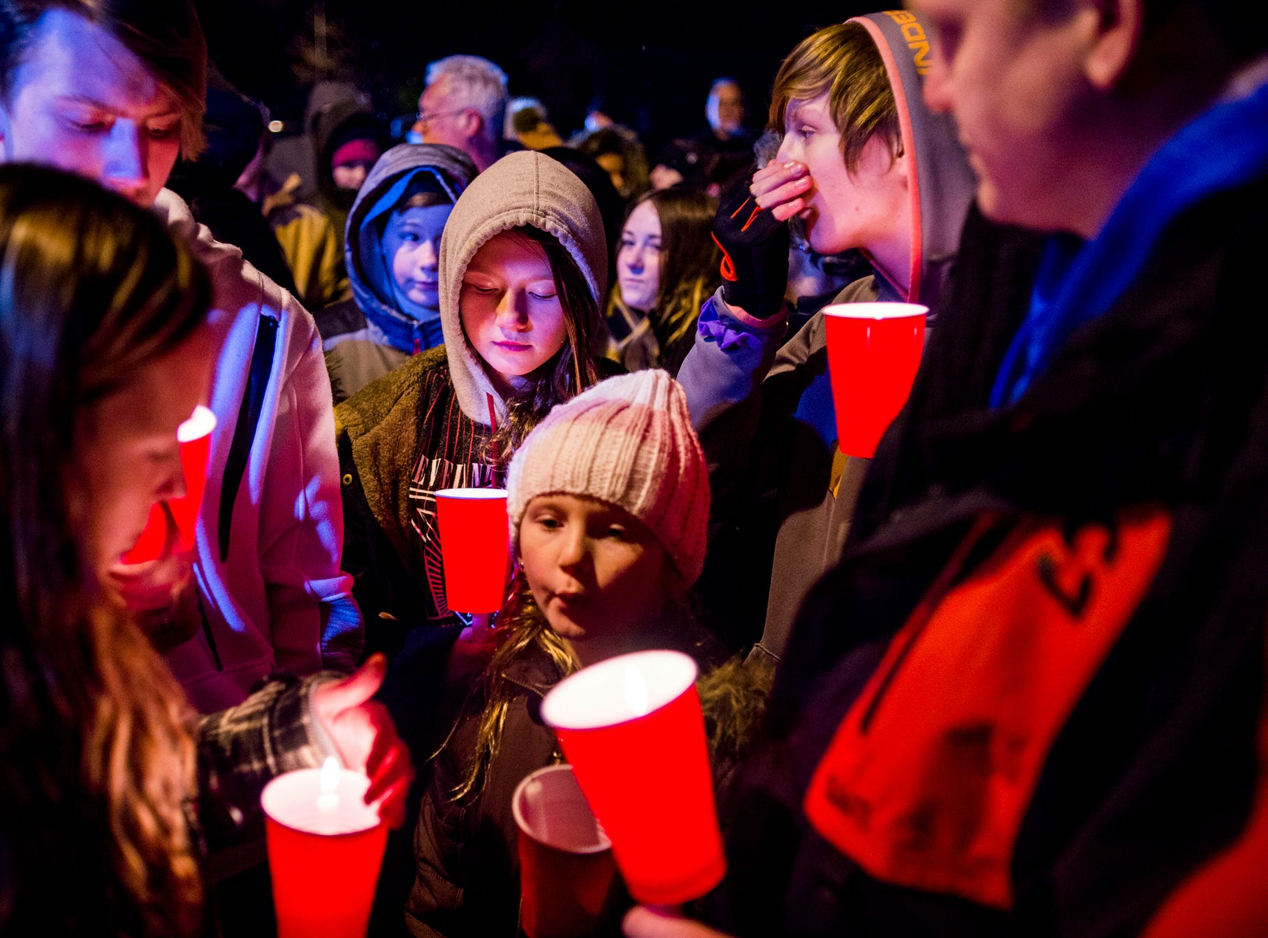 Makenzie Craven, 10, of Imlay City, bows her head alongside her family as she commemorates the lives of several children who died in an early morning fire at a mobile home park Tuesday, Feb. 26, 2019, in Imlay City, Michigan. Other Craven family members pictured include Makenzie's mother Melissa, father Michael Sr., sister Millie and brothers Michael Jr. and Haiden.