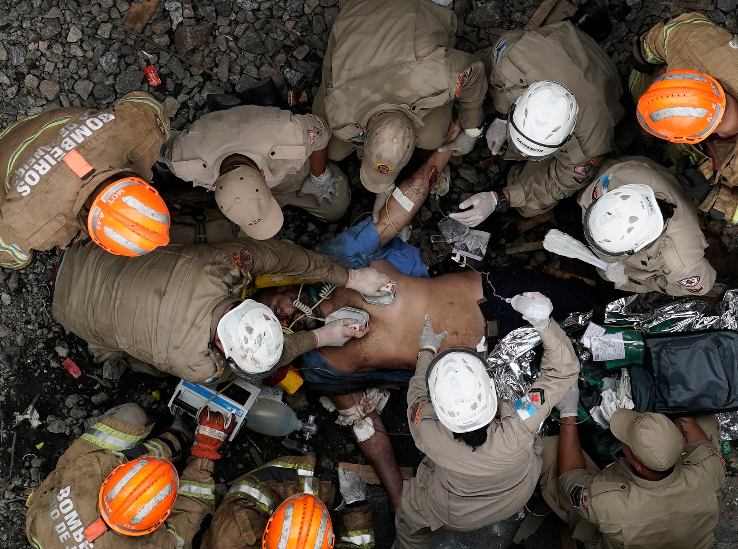 Firefighters work to resuscitate the driver of a commuter train that collided  with another train in Sao Cristovao station, in Rio de Janeiro, Brazil, Wednesday, Feb. 27, 2019. Firefighters worked for over six hours to rescue the train's driver, who was caught under the wreckage.