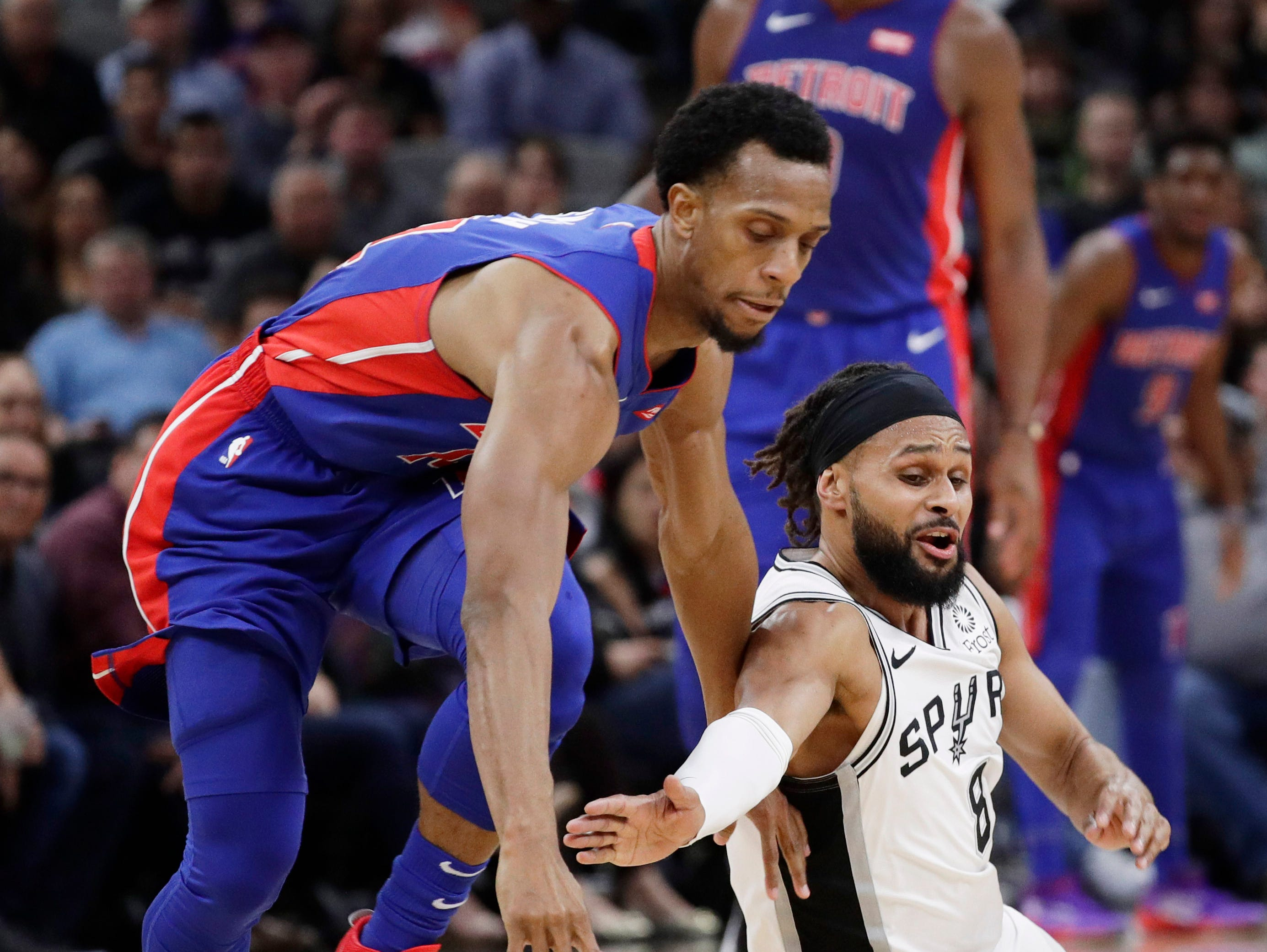 Detroit Pistons guard Ish Smith, left, and San Antonio Spurs guard Patty Mills (8) chase a loose ball during the second half.