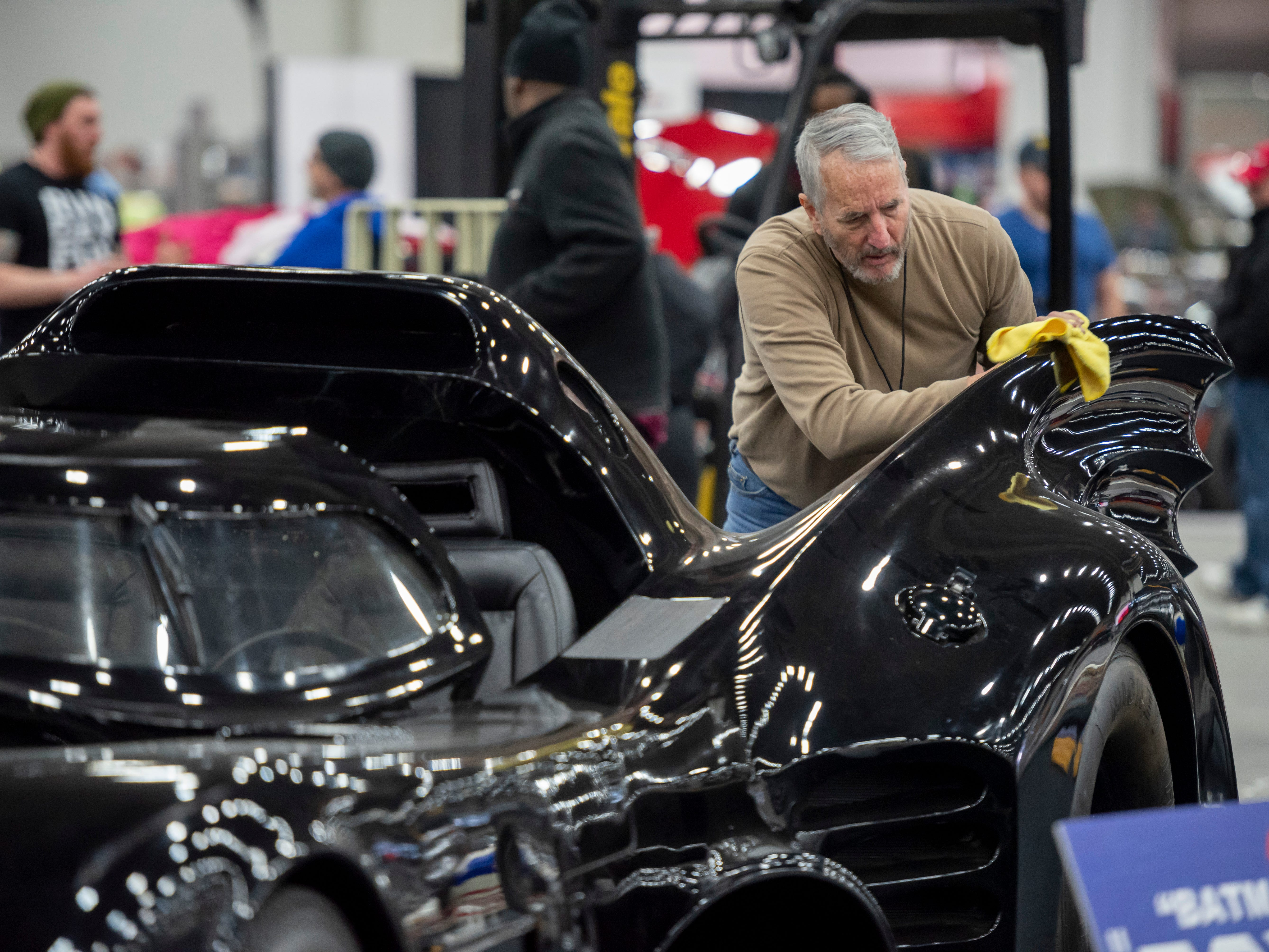 "John Davidson, of Louisville, Kentucky, polishes the Batmobile movie prop from the movie ""Batman Returns,"" owned by Carl Casper."