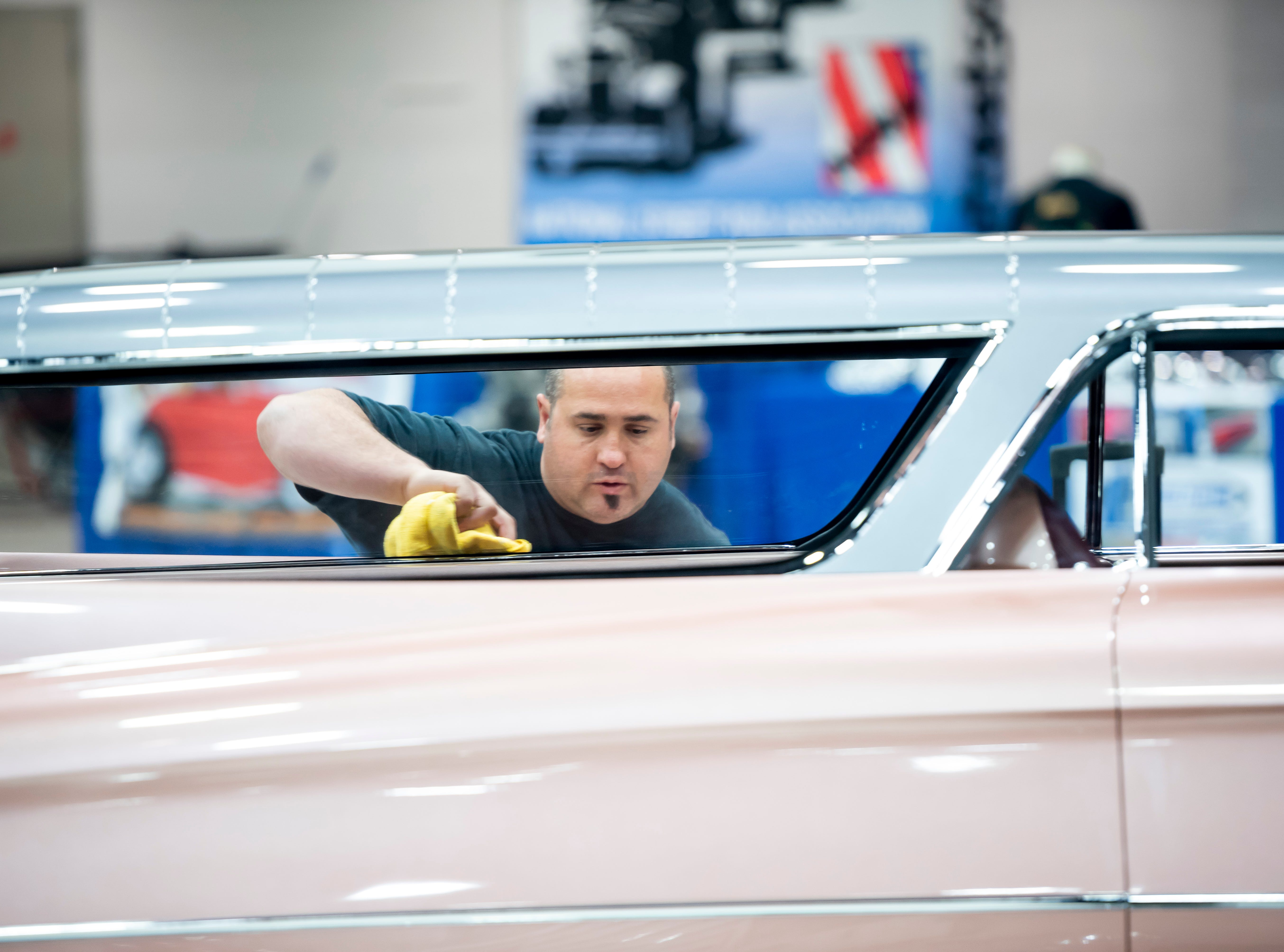 Jordan Quintal, an employee of Super Rides by Jordan, of San Diego, polishes a 1959 Cadillac, nicknamed Cadmad, owned by Steve Barton.