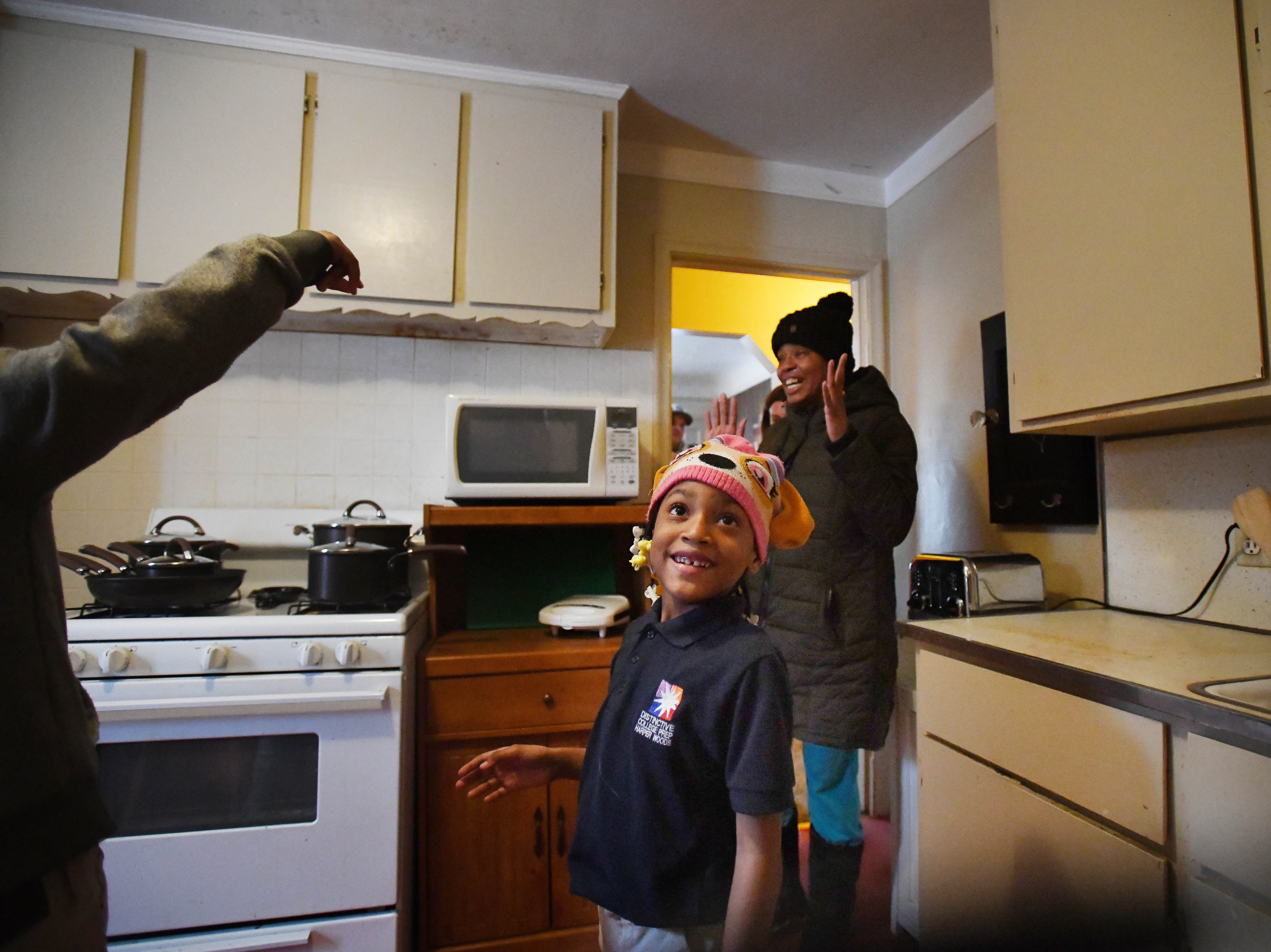 Ja'Kayla, 7, and her mother Jamiliah Powers-McCoy make their way into their newly renovated kitchen.