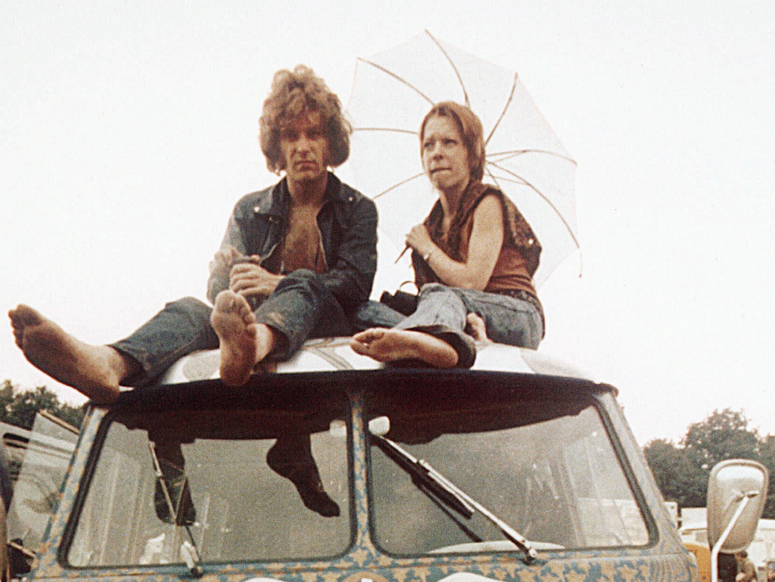 Concert-goers sit on the roof of a Volkswagen bus at the Woodstock Music and Arts Fair at Bethel, N.Y., in mid-August 1969. The three-day concert attracted hundreds of thousands of people, and became a landmark cultural event of the late '60s.