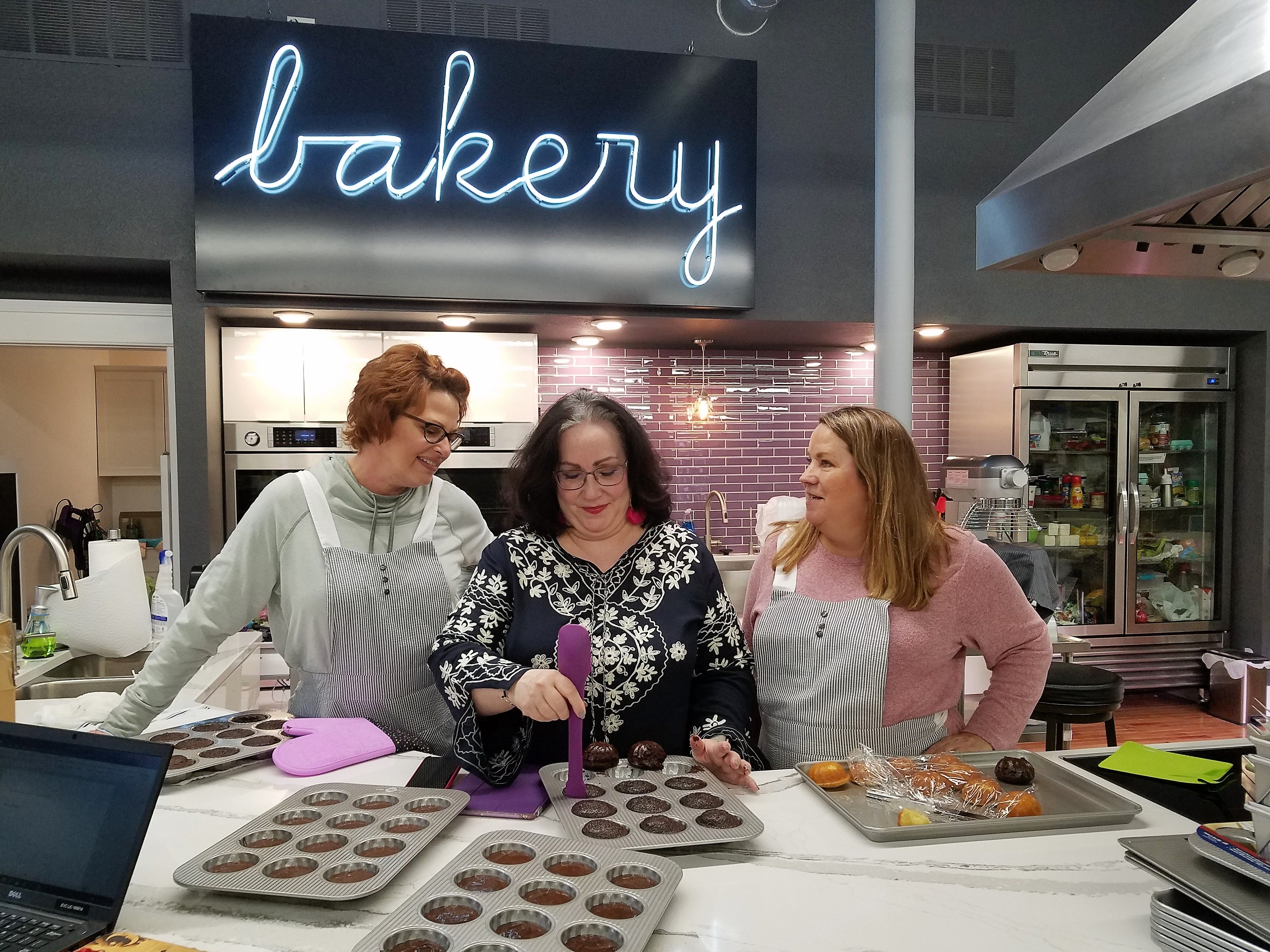 Capers Emporium owner Mary Beth Guard, center, with Jennifer Miller, left, and Diana Mathews, bake up chocolate and vanilla Capers Cakes in the Capers kitchen.