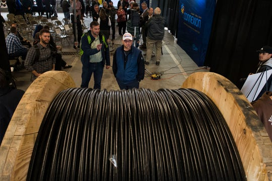 Software developer and remote employee for Arizona State University Steve Huard, center, checks out the gauge of wire on a spool of fiber optic cable during a groundbreaking celebration for the Connexion municipal broadband buildout on Thursday, Feb. 28, 2019, in Fort Collins, Colo.