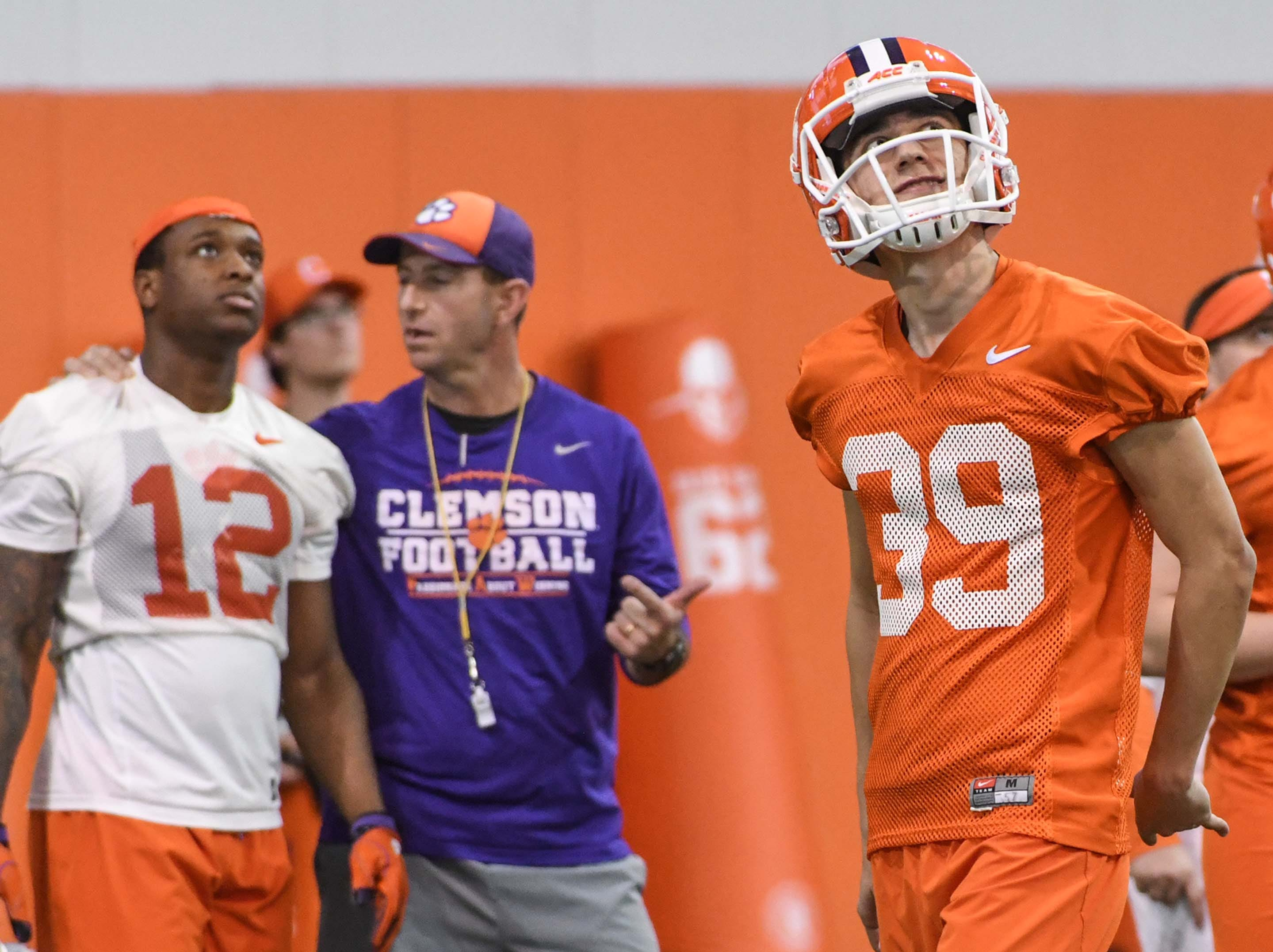 Clemson punter Aidan Swanson(39) watches his punt hit the roof of the indoor facility near defensive back K'Von Wallace (12) and head coach Dabo Swinney during the first practice at the Clemson Indoor Practice Facility in Clemson Wednesday, February 27, 2019.