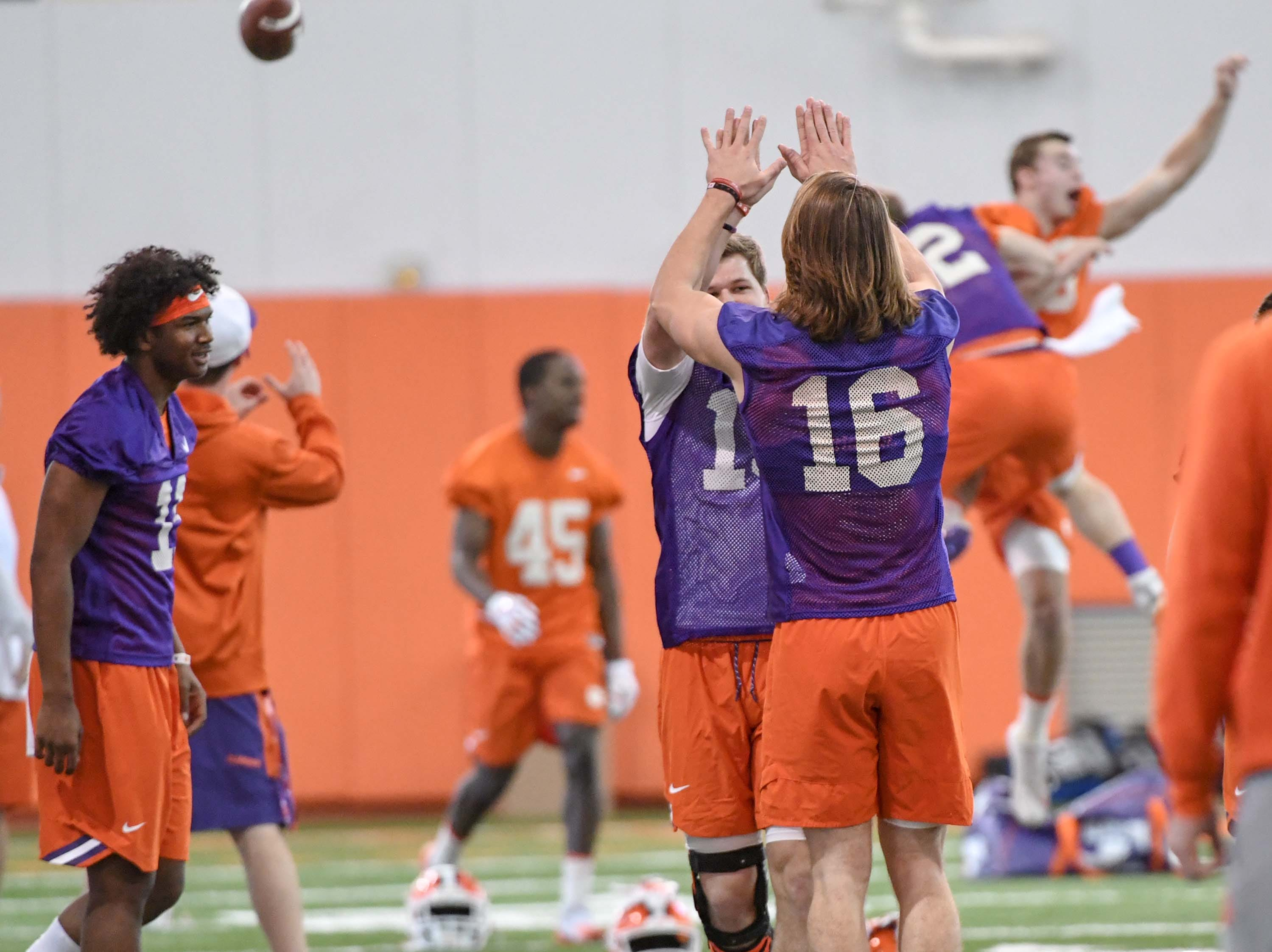 Clemson quarterback Taisun Phommachanh(11), left, a new and early enrollee able to participate in spring practice, watches veterans quarterback Patrick McClure (15) and quarterback Trevor Lawrence (16) high five each other at the beginning of the first practice at the Clemson Indoor Practice Facility in Clemson Wednesday, February 27, 2019.
