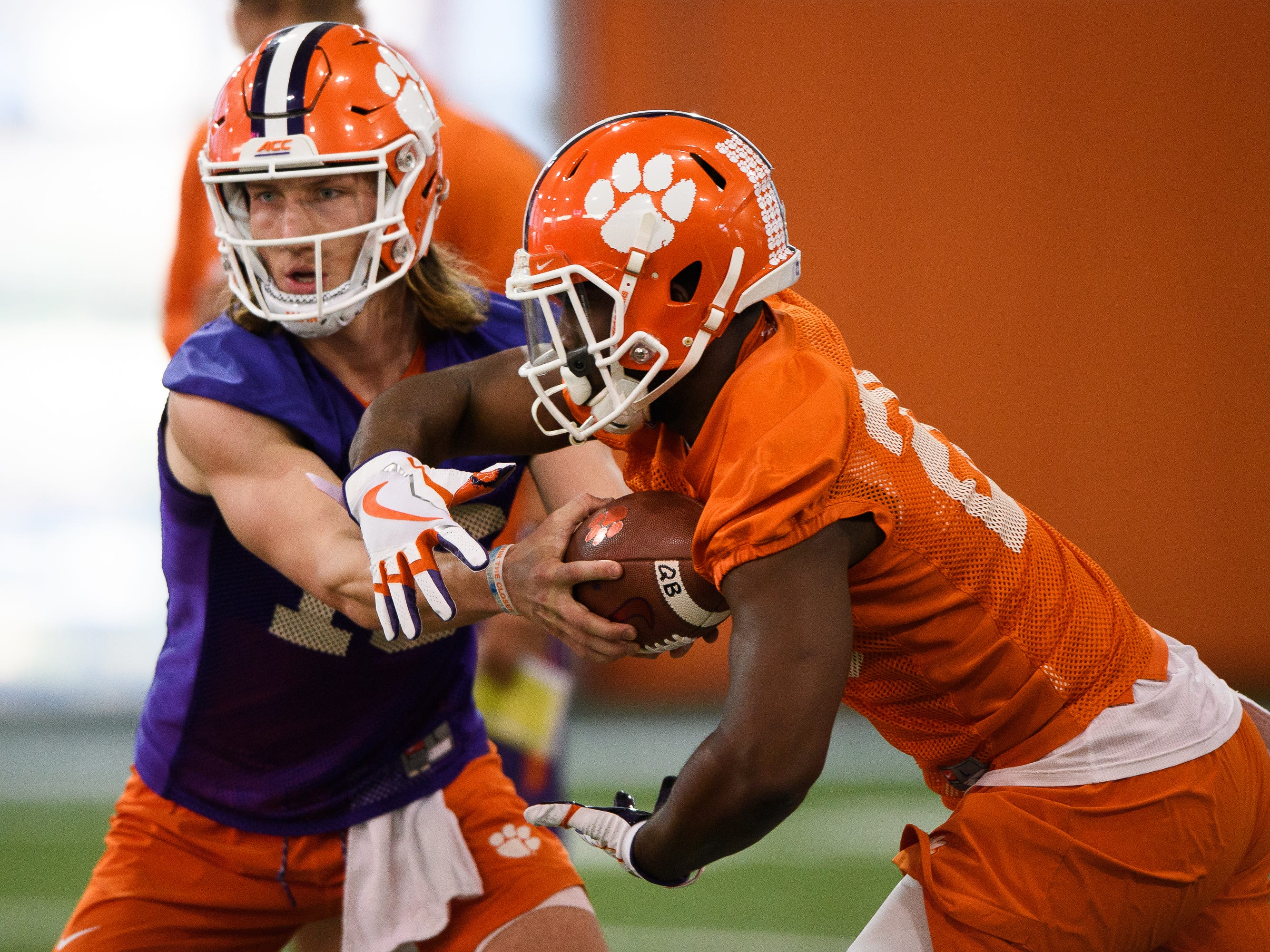 Clemson quarterback Trevor Lawrence (16) hands the ball to running back Tavien Feaster (28) during practice at the Allen Reeves Football Complex on Wednesday, Feb. 27, 2019.