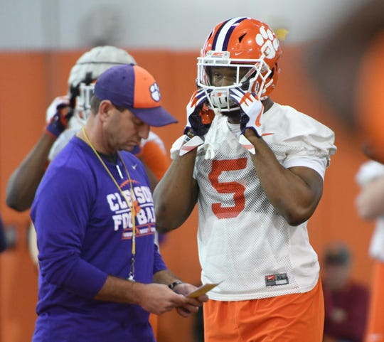 Clemson linebacker Shaq Smith (5) puts on his helmet near coach Dabo Swinney during the first practice at the Clemson Indoor Practice Facility in Clemson Wednesday, February 27, 2019.