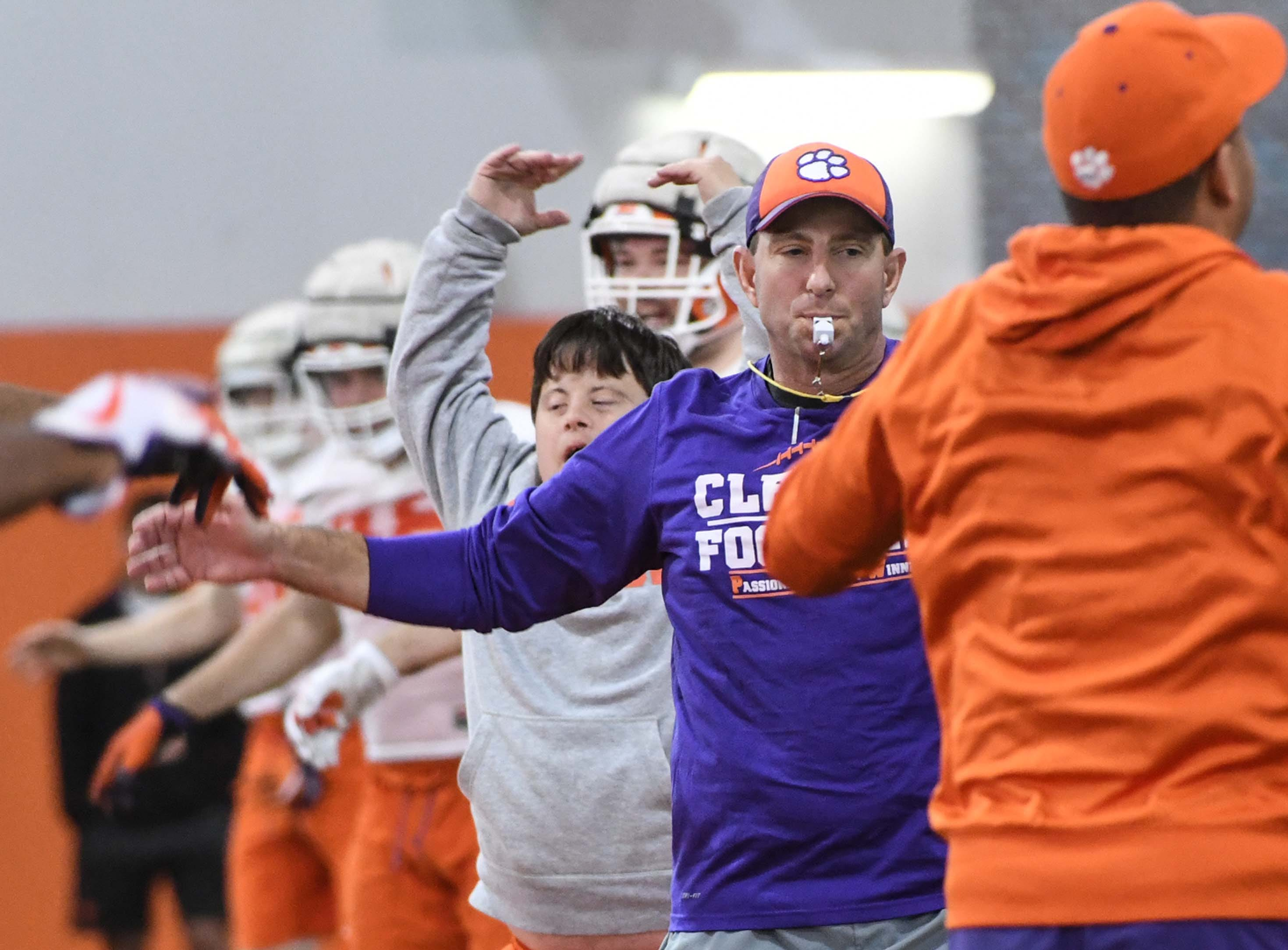 Clemson head coach Dabo Swinney leads jumping jacks during the first practice at the Clemson Indoor Practice Facility in Clemson Wednesday, February 27, 2019.