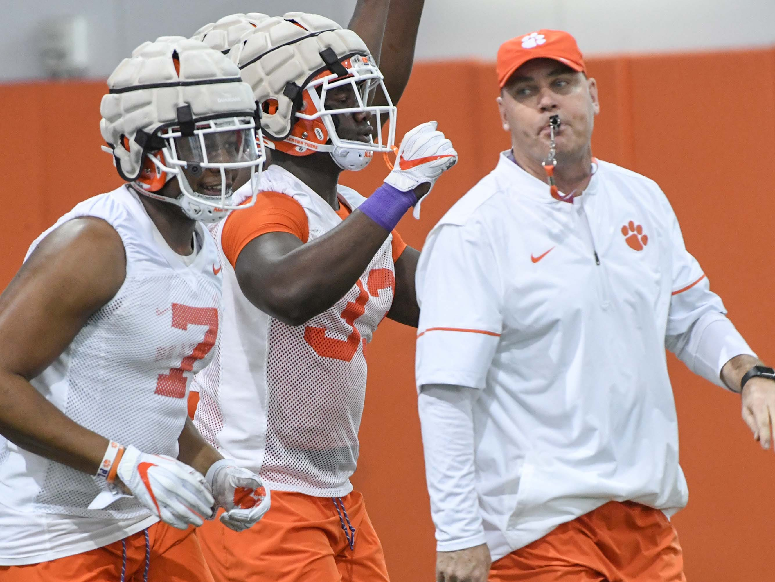 Clemson defensive end Justin Mascoll(7), left, returns with the number 7 jersey Austin Bryant wore on defense the year before, with newcomer defensive lineman Ruke Orhorhoro(33), near assistant head coach Danny Pearman during the first practice at the Clemson Indoor Practice Facility in Clemson Wednesday, February 27, 2019.