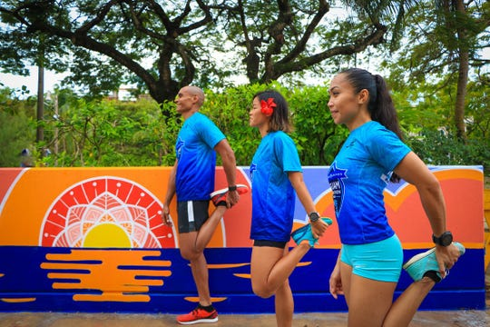 United Guam Marathon race ambassadors Leo Tkel, Manami Iijima and Rhea Macaluso stretch at the new United Airlines Guam Marathon's Runners' Oasis in front of the Pacific Islands Club parking garage in Tumon before their run. The mural was designed and painted by local artists Austin Domingo and Kristine Leigh Bactad.