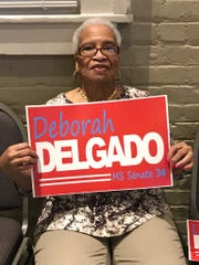 Jean Arnold of Hattiesburg holds a sign announcing Hattiesburg Councilwoman Deborah Delgado is running for state Senate on Wednesday, Feb. 27, 2019, at Laurel Train Depot.