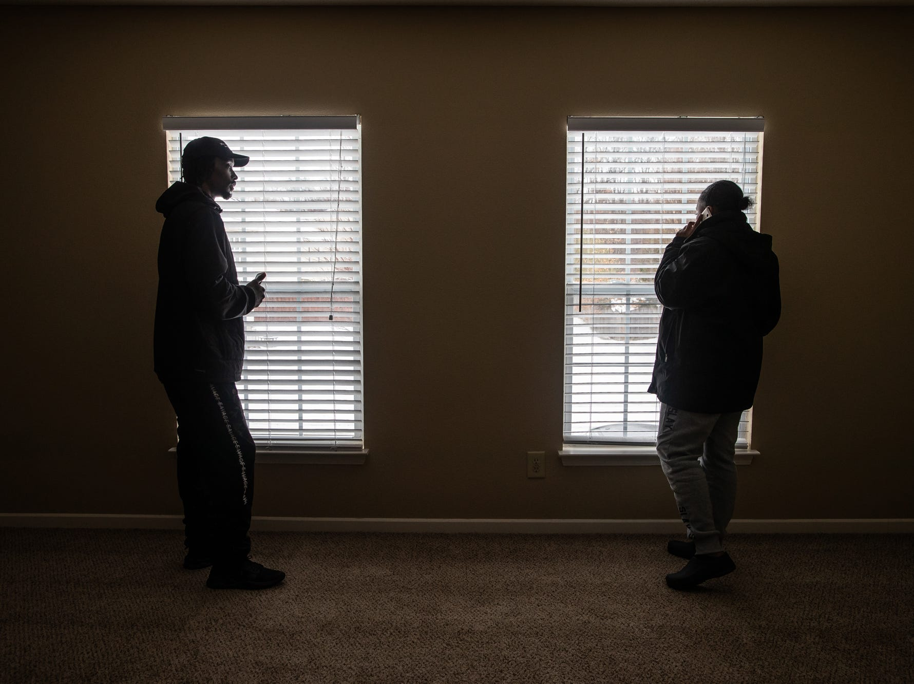 """Charles and Latasha look out the windows in the master bedroom of a home they are attempting to rent near Brownsburg, Ind., on Wednesday, Feb. 20, 2019. """"I've got Friday off of work. We can just come here after they get out of school,"""" said Latasha, about her three kids."""