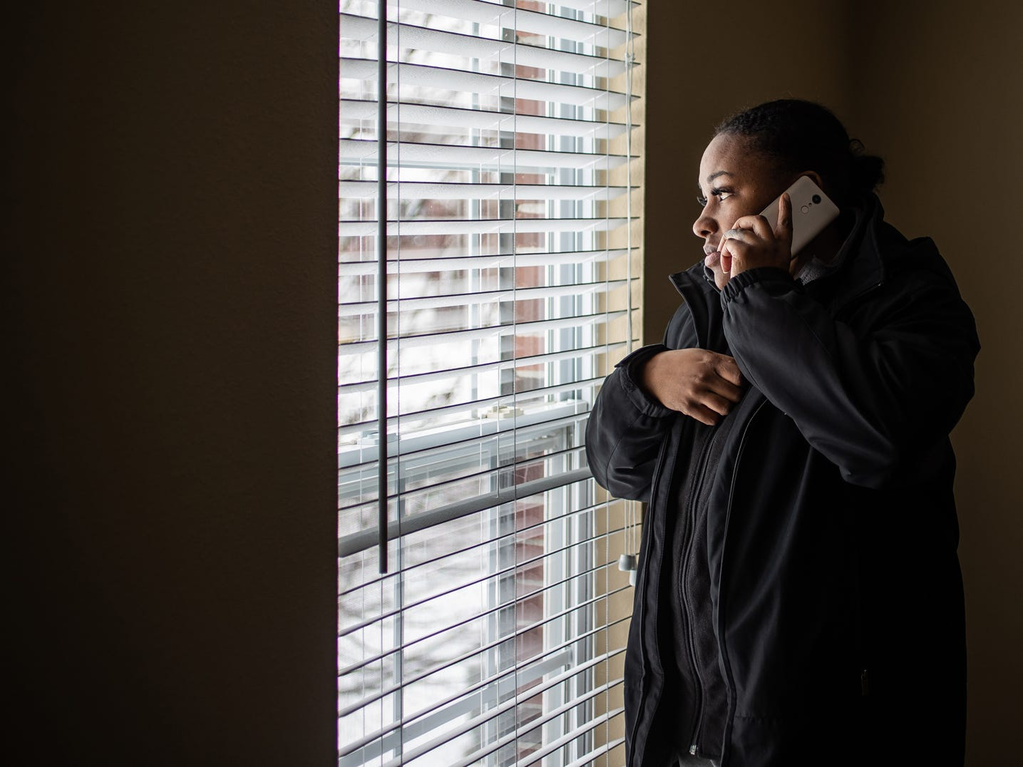 """Latasha Sanders takes a look out of a second floor window in the home she hopes to rent on Wednesday, Feb. 20, 2019. """"I mean, I like it. It's more than what I expected,"""" said Latasha. """"I'm excited but I'm not too excited yet until we actually have the paperwork, the lease with our signature on it."""" Sanders would later find out a man was attempting to scam her."""