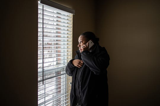 Latasha Sanders takes a look out of a second floor window in a home she hopes to rent.