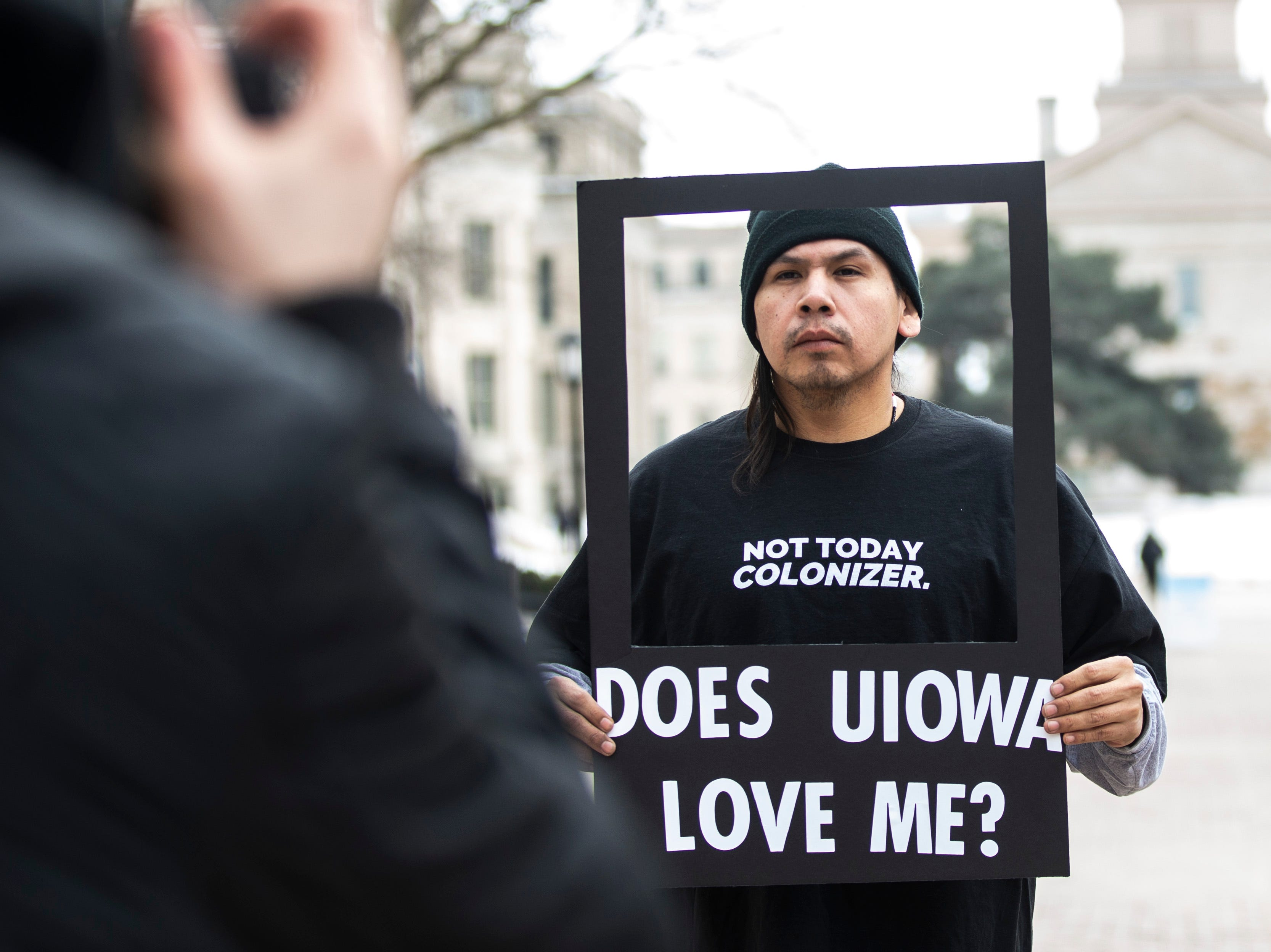 """University of Iowa senior Dawson Davenport holds a frame while wearing a shirt reading, """"Not today colonizer."""" as he has his photo taken during a """"speak out"""" event organized by the """"#DoesUIowaLoveMe"""" group on Thursday, Feb. 28, 2019, along the T. Anne Cleary Walkway on the University of Iowa campus in Iowa City, Iowa."""