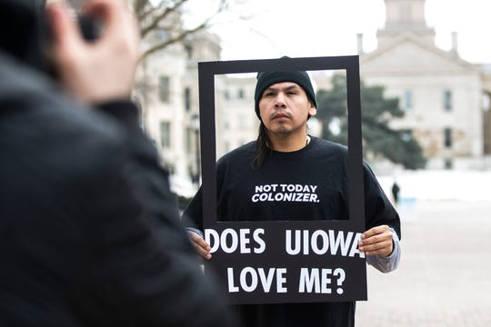 "University of Iowa senior Dawson Davenport holds a frame while wearing a shirt reading, ""Not today colonizer."" as he has his photo taken during a ""speak out"" event organized by the ""#DoesUIowaLoveMe"" group on Thursday, Feb. 28, 2019, along the T. Anne Cleary Walkway on the University of Iowa campus in Iowa City, Iowa."