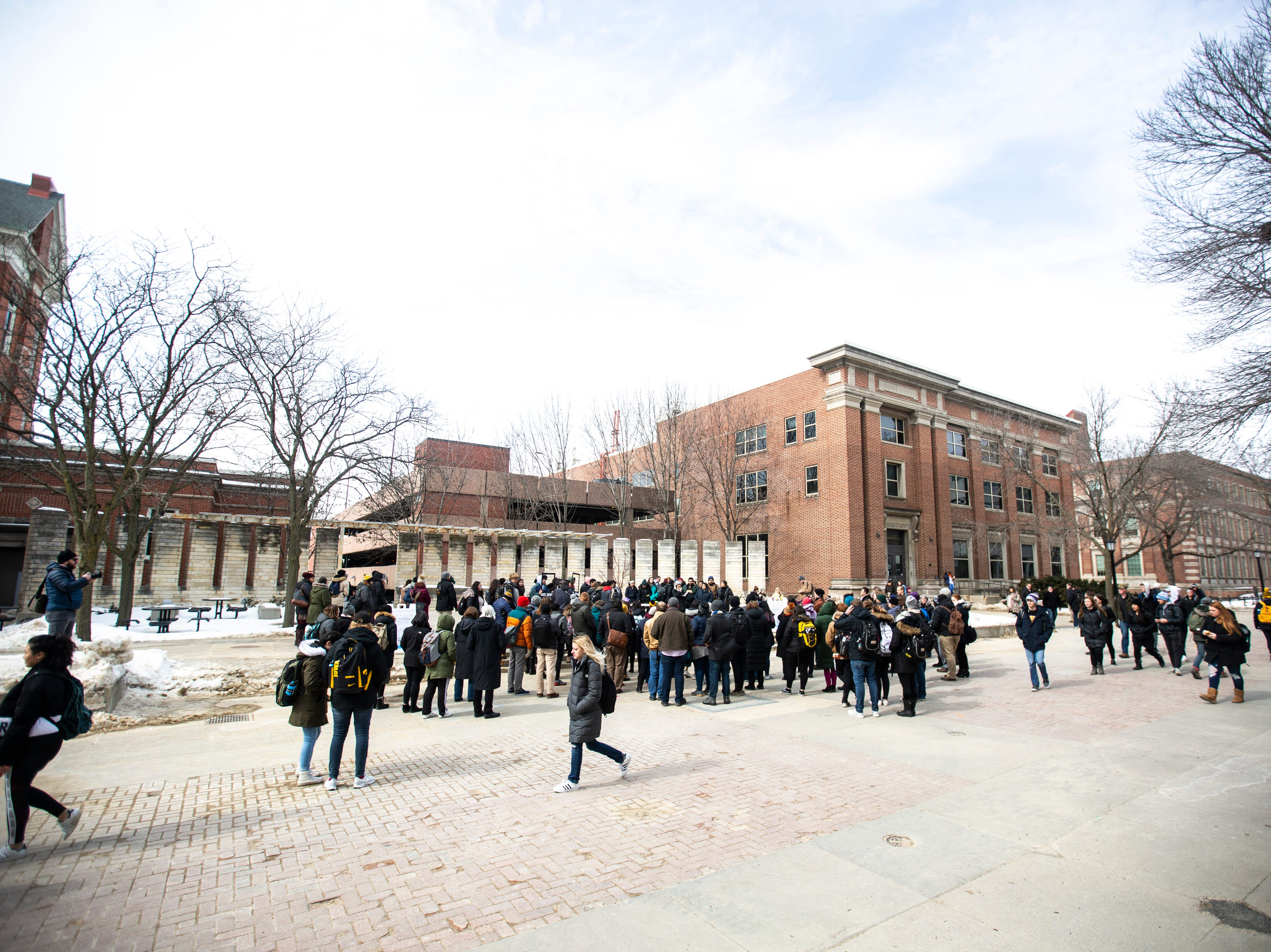 """Students gather during a """"speak out"""" event organized by the """"#DoesUIowaLoveMe"""" group on Thursday, Feb. 28, 2019, along the T. Anne Cleary Walkway on the University of Iowa campus in Iowa City, Iowa."""