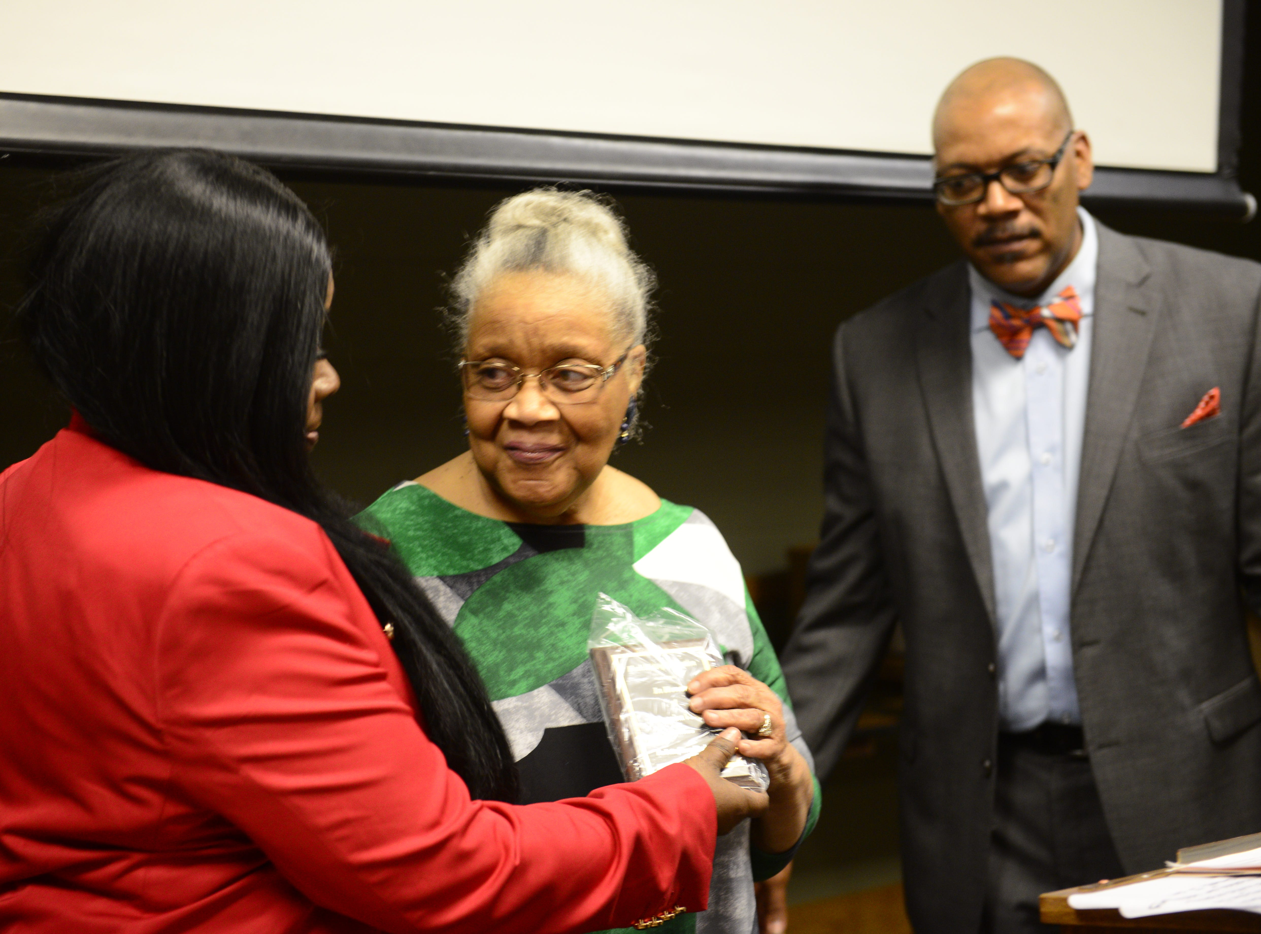 Angela Parks (left) gives Thomasina Vaught (center) her an award at the Jackson-Madison County Library in Jackson, Tenn. Feb. 27, 2019
