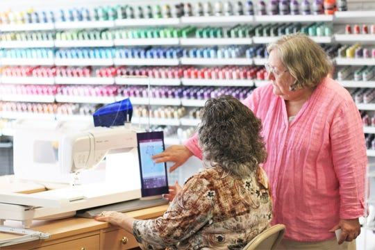 Martha Laszlo shows customer Susan Harris one of the Wi-Fi enabled sewing machines at Sew 'N Vac in Fountain City on Feb. 28.