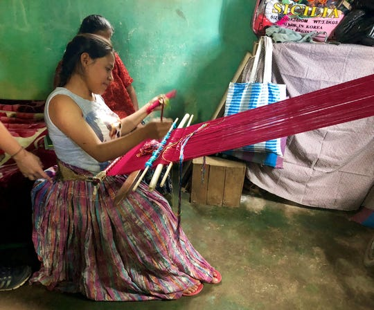 A woman in Chicoyoj I, Guatemala, weaves on a portable loom attached to her waist on one end and the window of her home on the other. It takes her about 45 days of work to complete a traditional blouse.