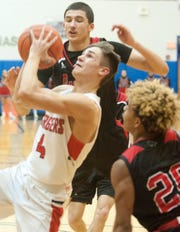 Bullitt East guard Thomas Wiseheart drives between Pleasure Ridge Park forward Shawn Paris, top, and Pleasure Ridge Park guard James Taylor, right.  Wiseheart sunk a 3-point shot with seconds to go to beat PRP, 45-42 in the Region 6 semi-final. 27 February 2019