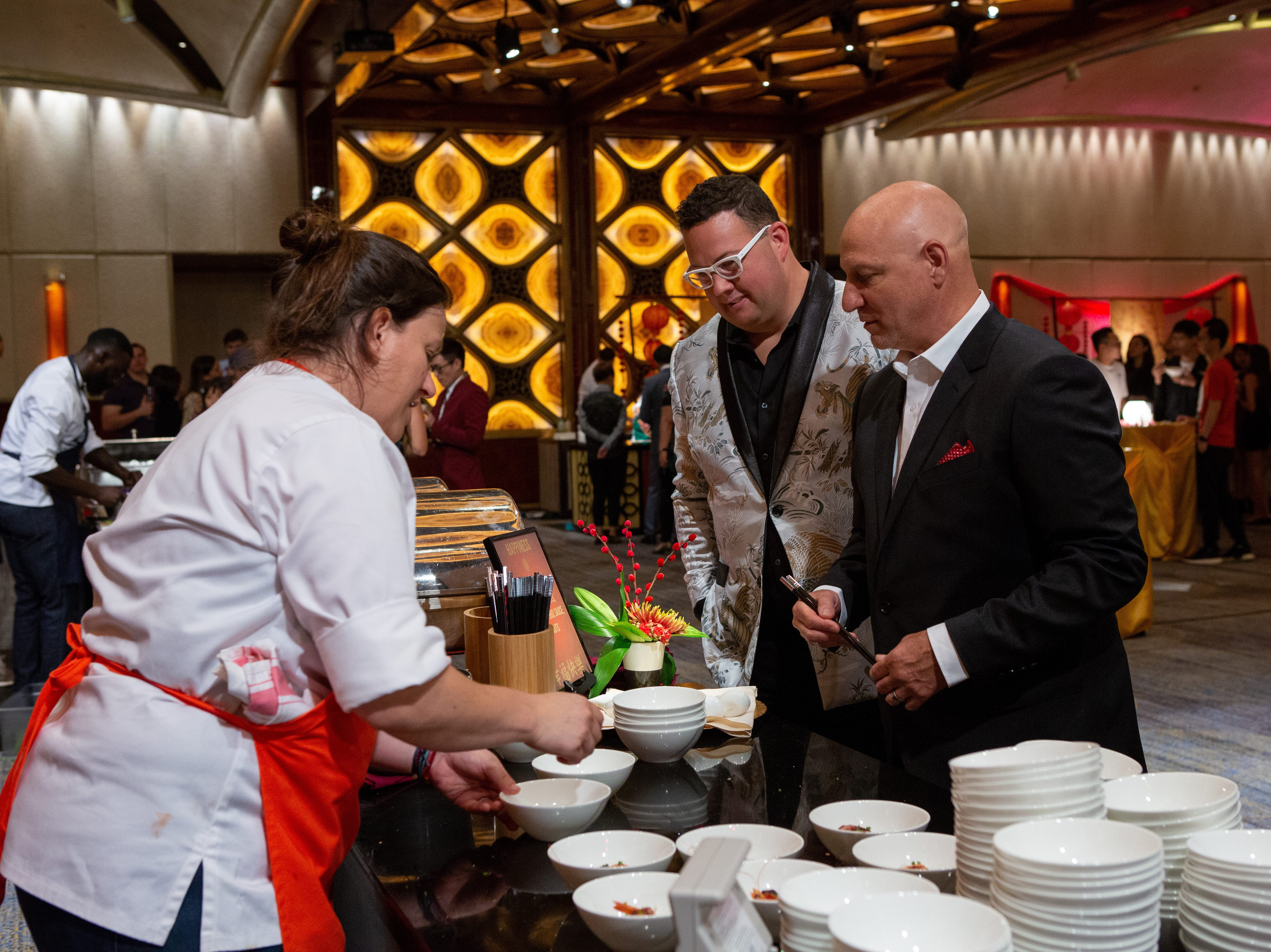 "(From left to right): Contestant Sara Bradley serves her dish to judges Graham Elliott and Tom Collicchio on ""Holy Macau!"" episode 13 of Bravo's 'Top Chef:' Kentucky season."
