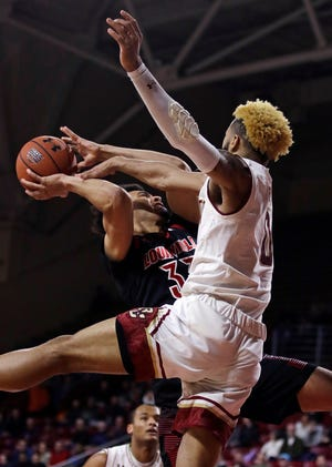 Boston College guard Ky Bowman, right, blocks a shot by Louisville forward Jordan Nwora, left, during the first half of an NCAA college basketball game in Boston, Wednesday, Feb. 27, 2019.