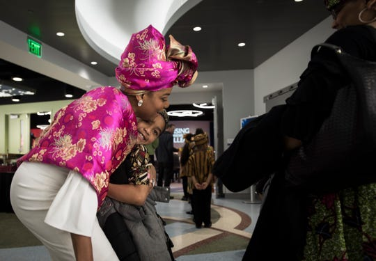 Kendall Taylor, a second-grader at Pam's Academy of Champions in Lansing, hugs Lansing Community College Trustee Angela Mathews, Thursday, Feb. 28, 2019, before a painting of Malcolm X was unveiled as part of LCC's kickoff a its year-long participation in the national 400 Years of African American History Commission.