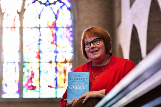 "The Rev. Karen C. Lewis, the rector at St. Paul's Episcopal Church in Lansing, shows the book ""Grateful"" in the church sanctuary Feb. 28, 2019. The author, Diana Butler Bass, will speak about gratitude at a forum, workshop and church services March 8-10."