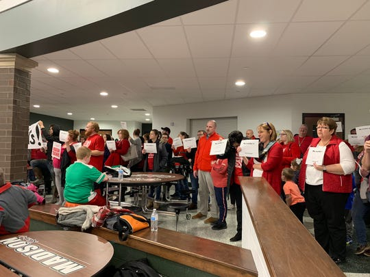 Madison teachers and supporters, at a school board meeting Wednesday, hold signs indicating the number of hours they've worked outside of the hours stipulated in their contract.
