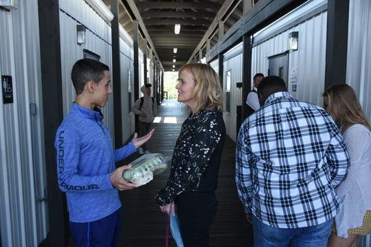 Principal Melissa Scott speaks to a student between rows of temporary classroom buildings. Marco Island Academy is embarking on a capital campaign to raise millions of dollars and give the school a permanent home, after years of operating in prefab modules.