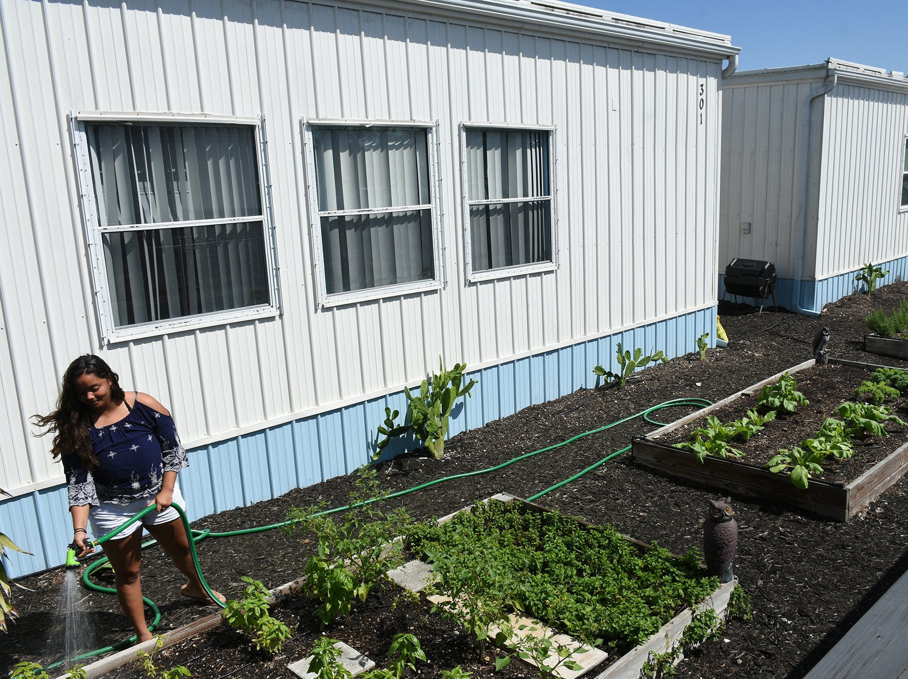 Junior Marissa Roach waters a garden in front of temporary classroom buildings. Marco Island Academy is embarking on a capital campaign to raise millions of dollars and give the school a permanent home, after years of operating in prefab modules.