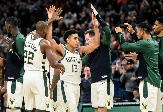 Nov 24, 2018; Milwaukee, WI, USA;  Milwaukee Bucks guard Malcolm Brogdon (13) celebrates with forward Khris Middleton (22) after scoring a 3-point basket late in the fourth quarter during the game against the San Antonio Spurs  at the Fiserv Forum. Mandatory Credit: Benny Sieu-USA TODAY Sports