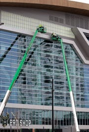 Workers prepare the exterior of Fiserv Forum in advance of the installation of a new sign.  Rick Wood/ Milwaukee Journal Sentinel ORG XMIT: 30097861A