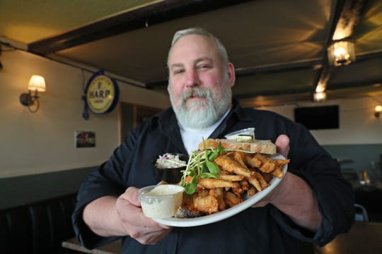 Co-owner Richard Heil holds a combo plate of fried smelt and rainbow trout at the Thistle & Shamrock, 3430 N. 84th St. The corner bar and restaurant has 21 varieties of fish on Fridays.