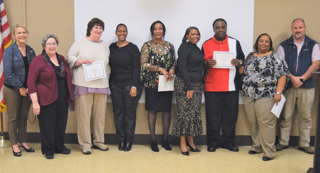 Janet Rainey and Ed German, holding certificates, are joined by friends, family members and school officials after being named MPS Employees of the Month on Tuesday, Feb. 26, 2019. At far left is Montgomery County Board of Education member Jannah Bailey, second from left is Board President Clare Weil, Superintendent Ann Roy Moore is at center, and Maintenance Director Lee McKenzie is at far right.