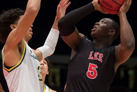 Lee's Deyunkrea Lewis (5) goes up for a shot over Mountain Brook's Colby Jones (3) during the Class 7A state semifinal at Legacy Arena in Birmingham, Ala., on Thursday, Feb. 28, 2019. Mountain Brook leads Lee 24-21 at halftime.