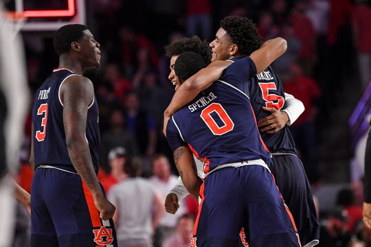Auburn players Chuma Okeke (5), Horace Spencer (0) and Danjel Purifoy (3) celebrate after beating Georgua at Stegeman Coliseum on Feb. 27, 2019, in Athens, Ga.