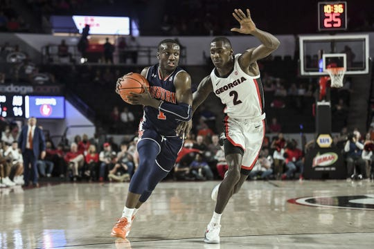 Auburn guard Jared Harper drives against Georgia defender Jordan Harris during a game at Stegeman Coliseum on Feb. 27, 2019, in Athens, Ga.